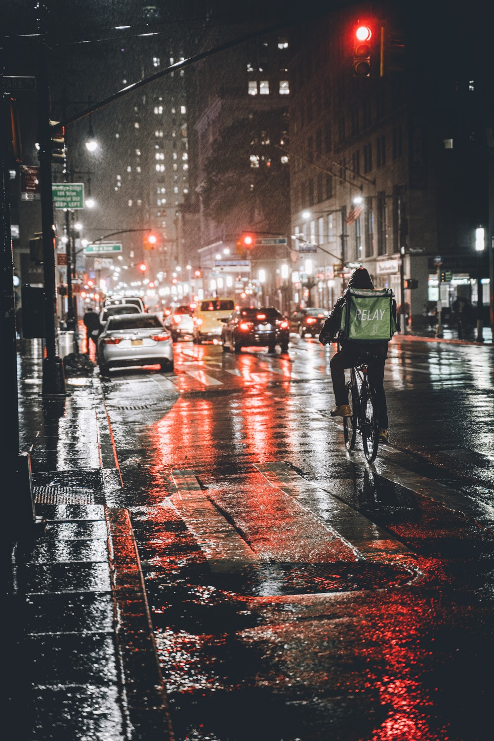 man in green jacket and black pants walking on street during night time