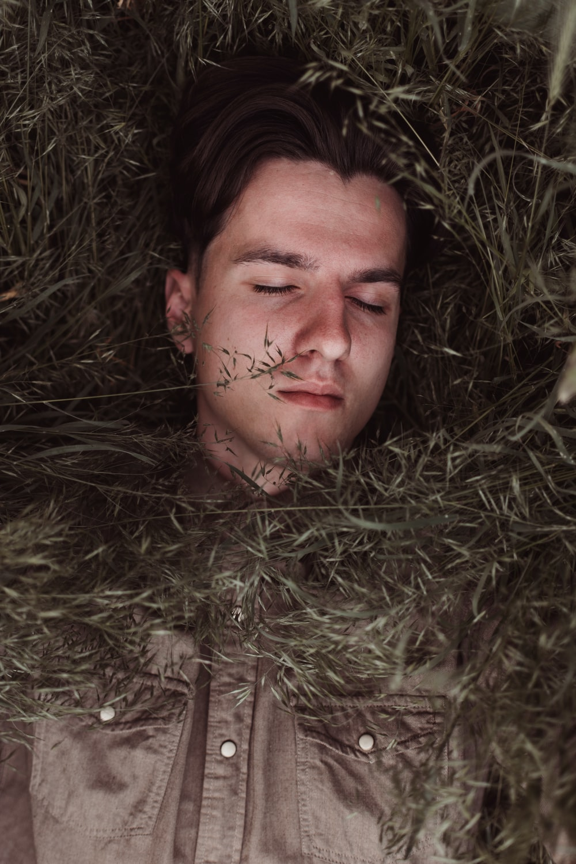 man lying on green grass