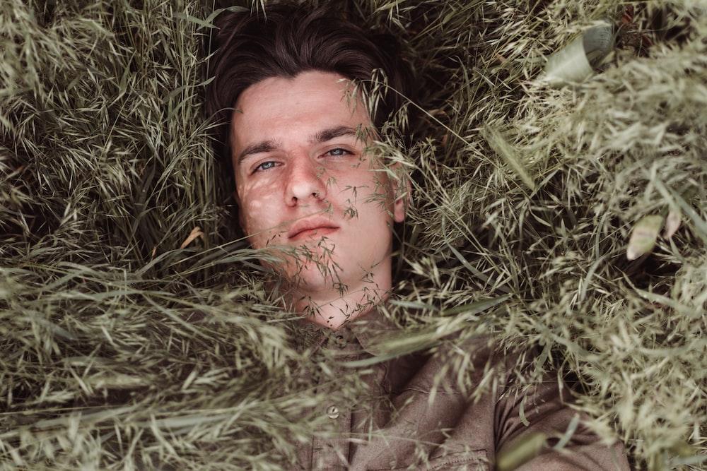 man lying on green grass during daytime