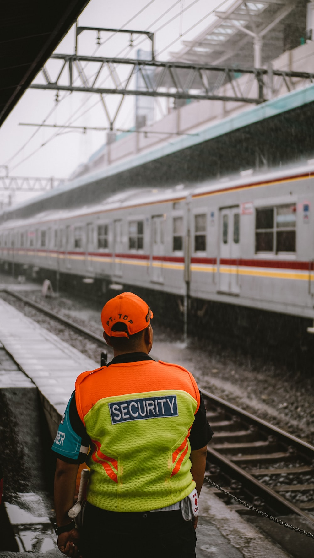 man in green and yellow shirt wearing orange cap standing on train station
