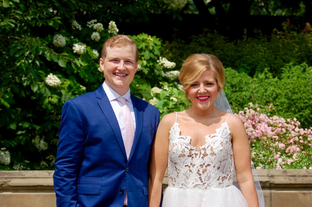 man in blue suit jacket beside woman in white floral lace sleeveless dress