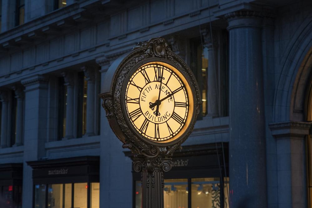 brown and white analog clock at 11 00