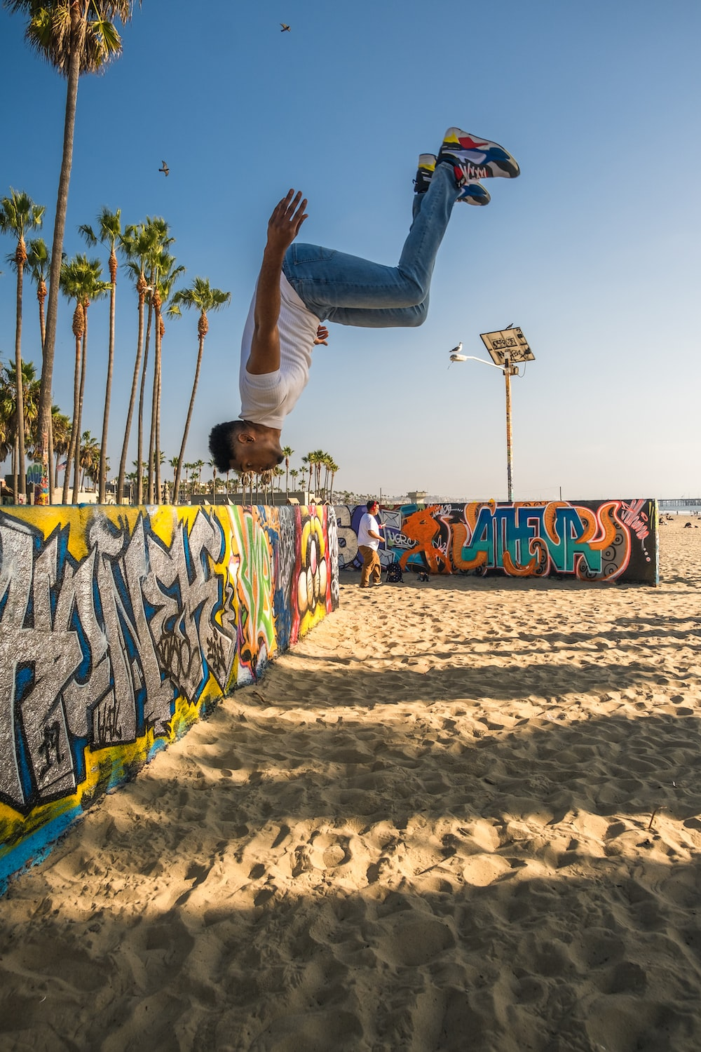 man in white t-shirt and black pants doing skateboard stunts on beach during daytime