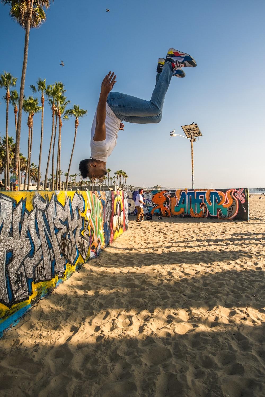 man in white t-shirt and black pants doing skateboard stunts on beach during daytime