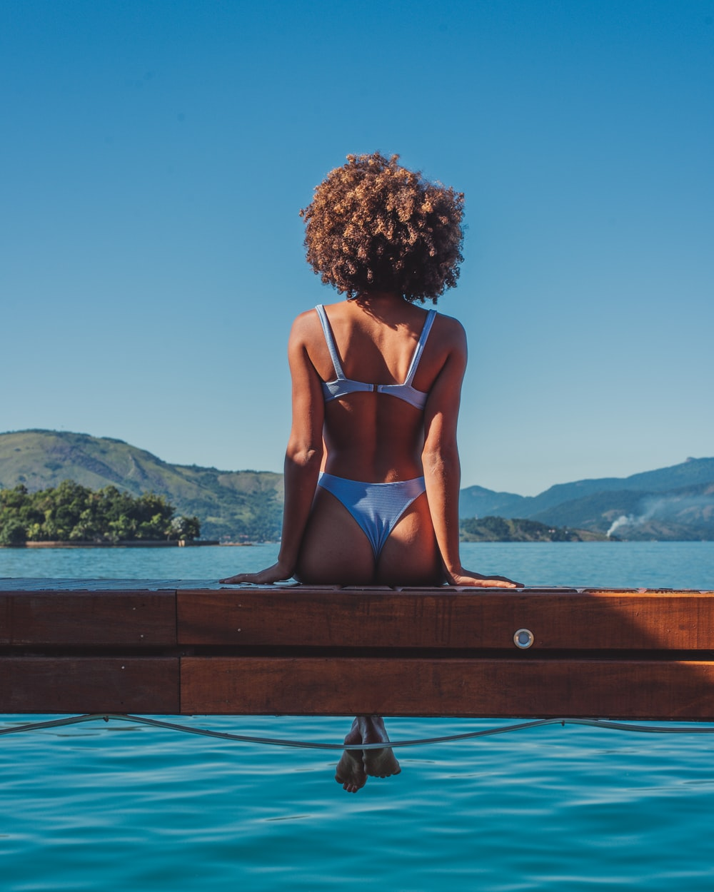 woman in blue bikini sitting on brown wooden bench during daytime