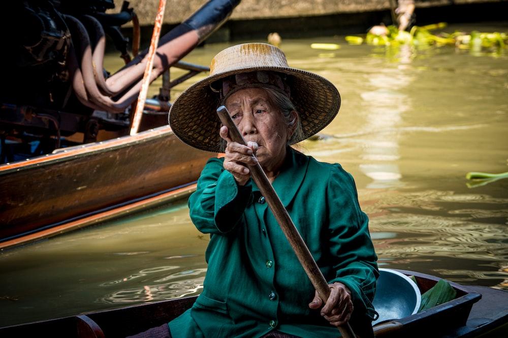 man in blue dress shirt wearing brown hat sitting on boat during daytime