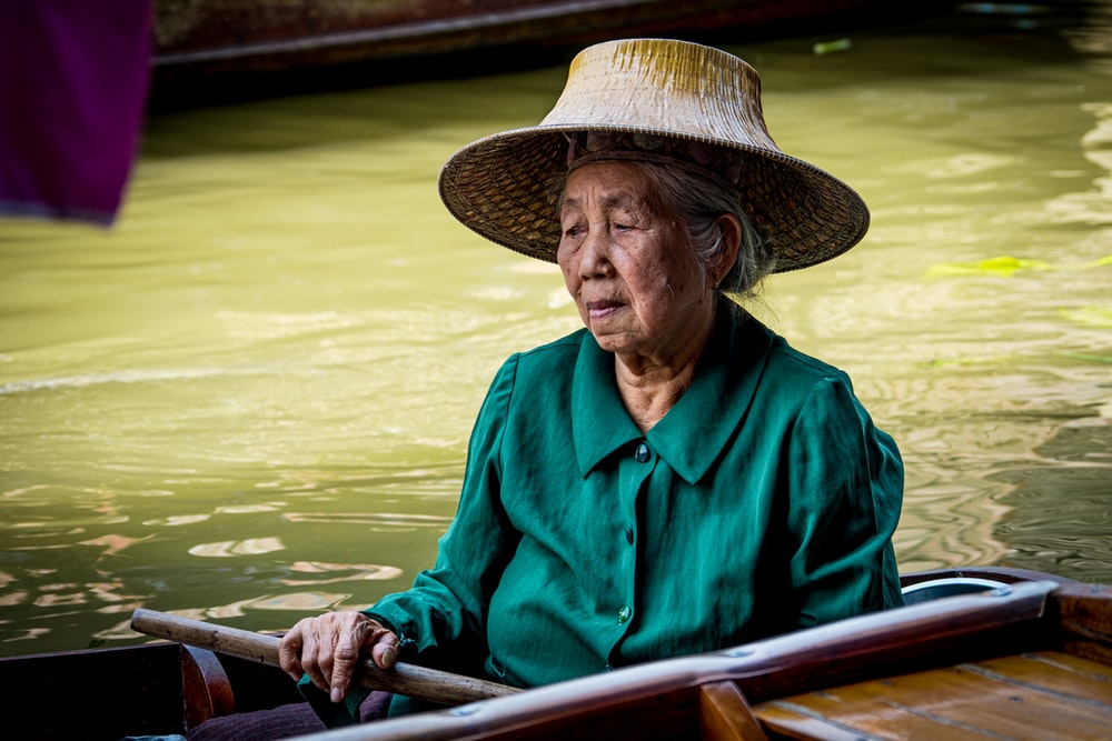 man in blue dress shirt wearing brown straw hat riding on boat during daytime
