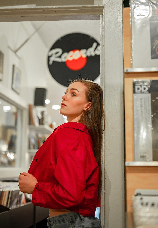 woman in red long sleeve shirt standing near glass window