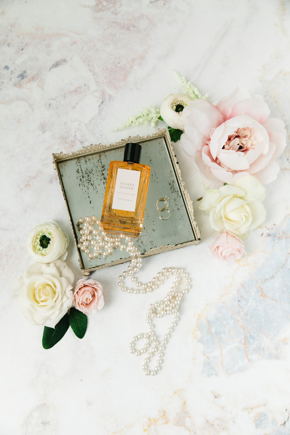 gold perfume bottle on white and pink floral textile