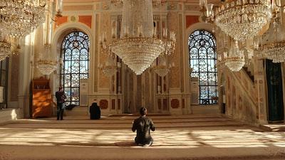 man in black jacket sitting on brown concrete floor religion teams background