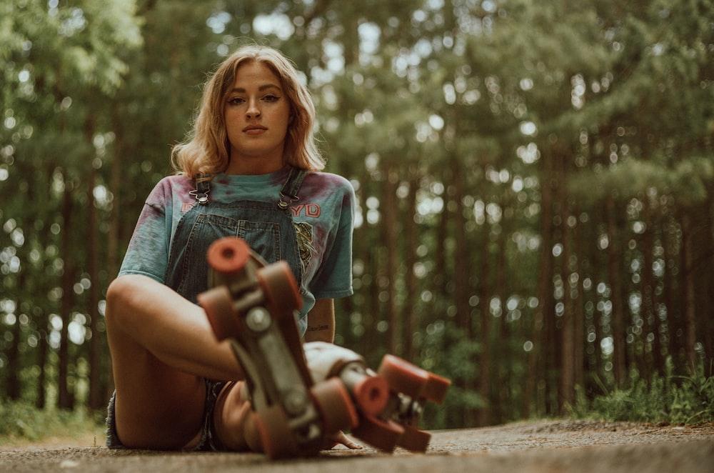 girl in green dress holding red toy gun