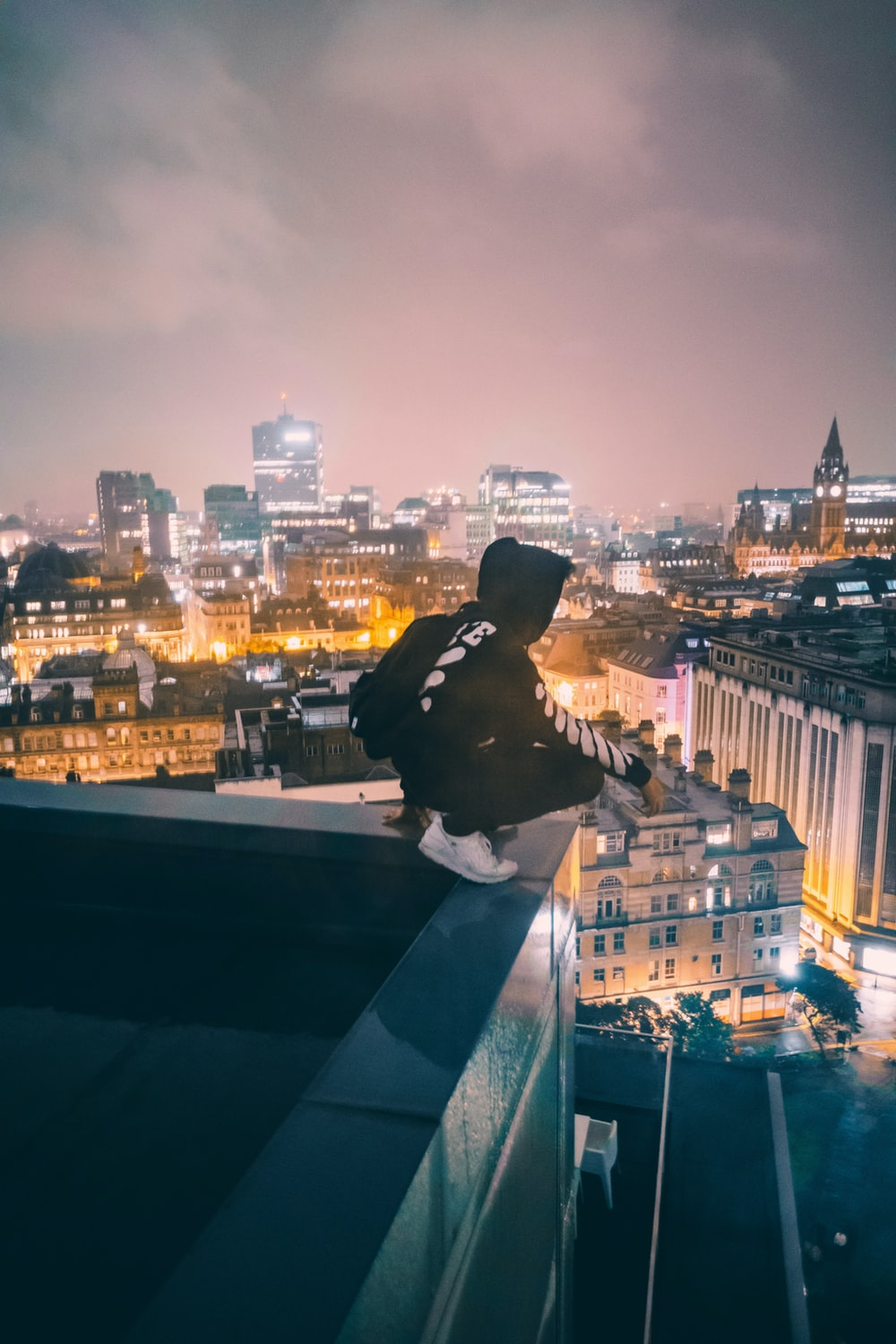 person in black hoodie and black knit cap sitting on top of building during daytime