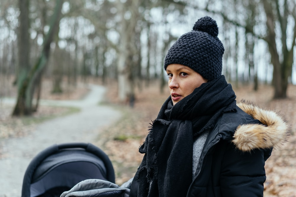 woman in black knit cap and black coat standing on road during daytime