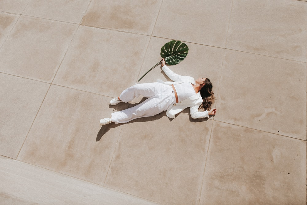 woman in white long sleeve shirt and white pants lying on green and white floor tiles