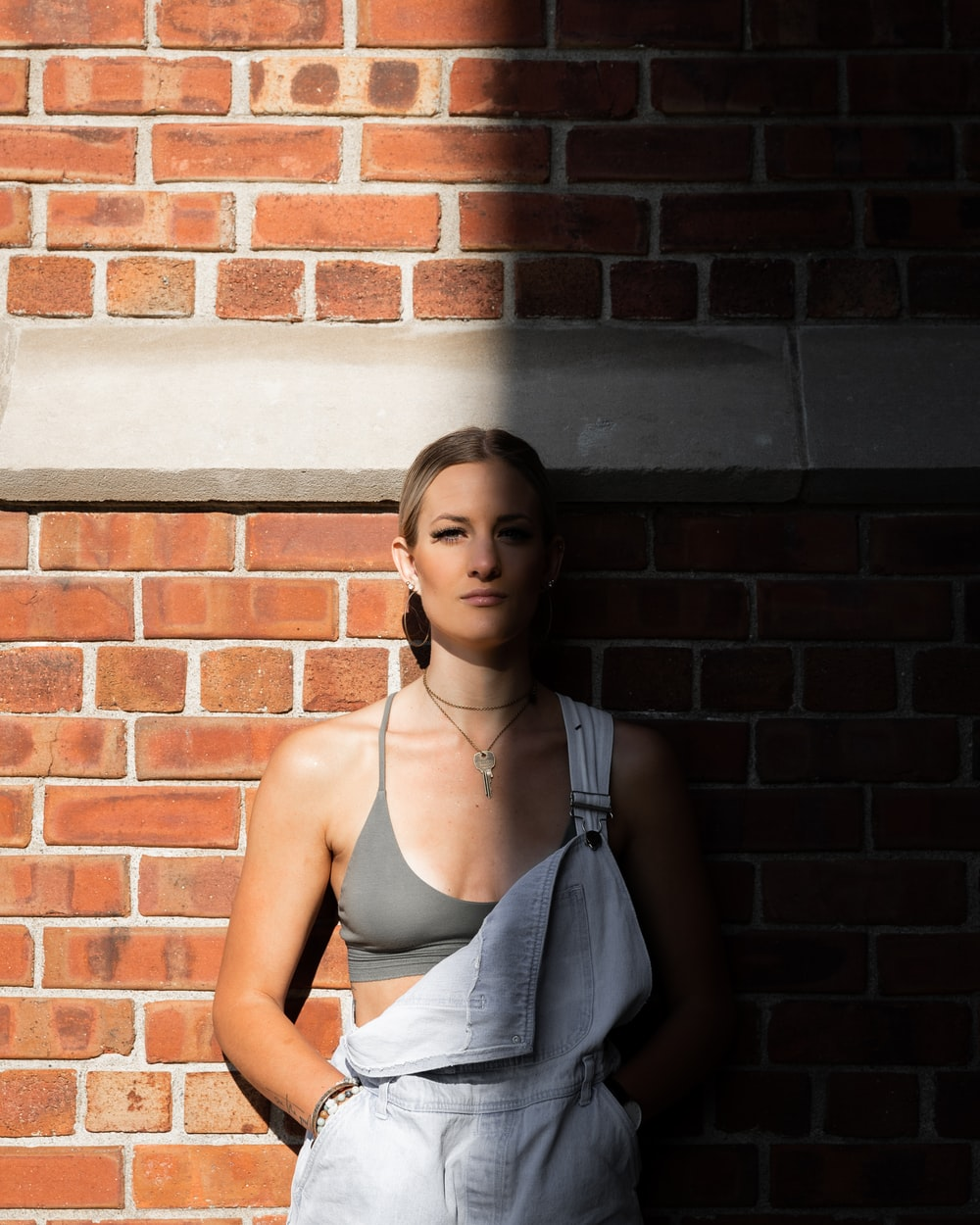 woman in gray spaghetti strap top leaning on brown brick wall