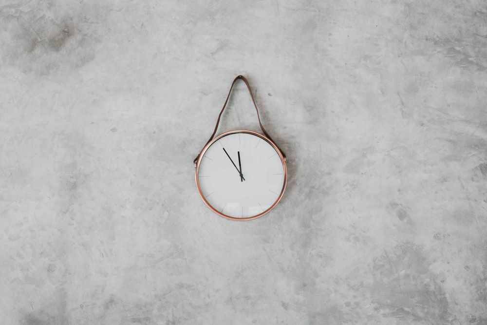 brown and white round analog wall clock