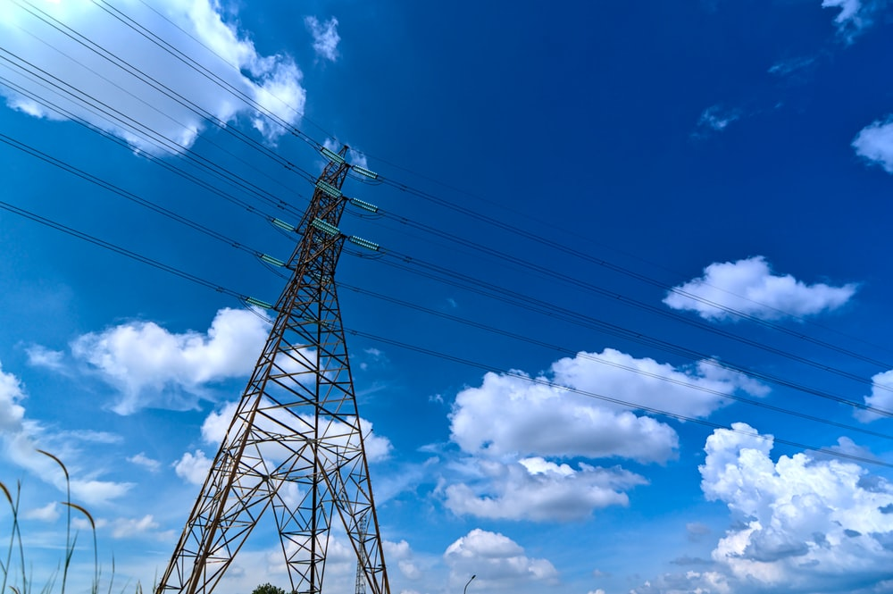 gray steel tower under blue sky and white clouds during daytime