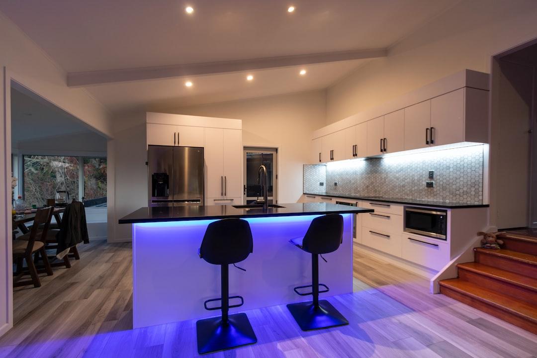 A modern white kitchen with led strip lighting, tiled wooden like flooring and a tile splashback