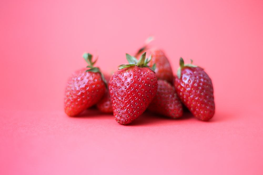 red strawberries on pink surface