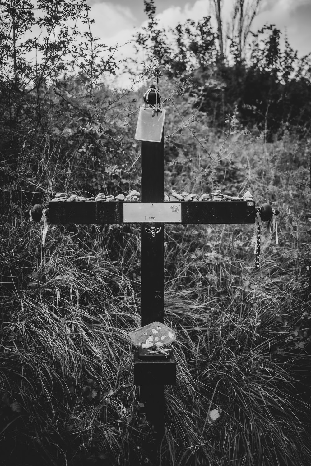 grayscale photo of cross in the middle of the forest