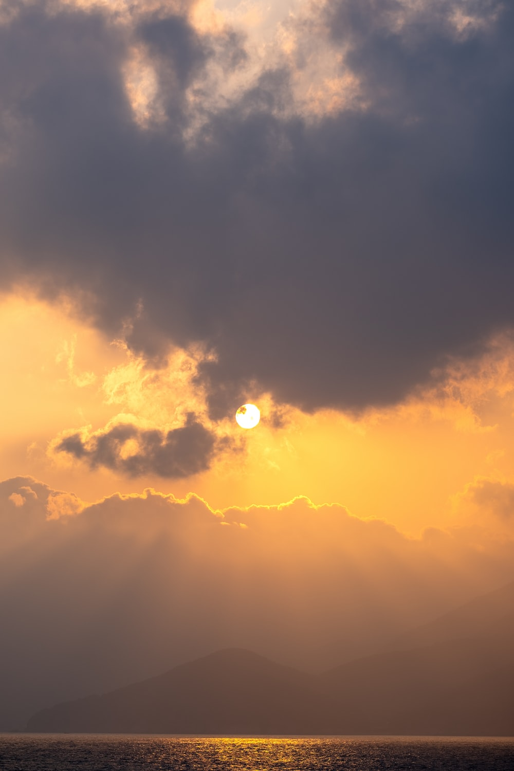 sun covered by clouds during sunset