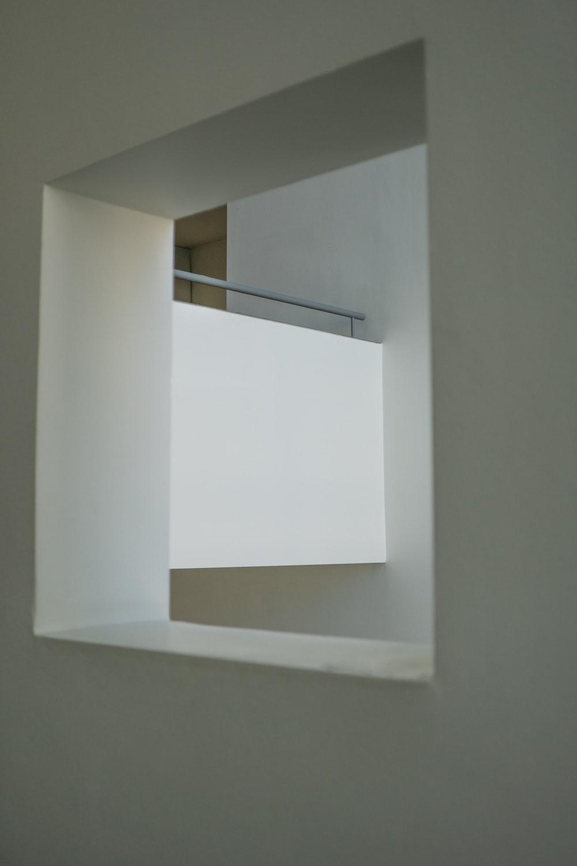 white wall mounted shelf on white wall