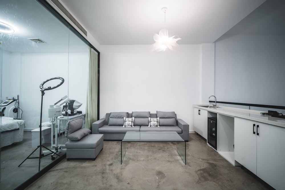 gray sectional couch beside white wooden table