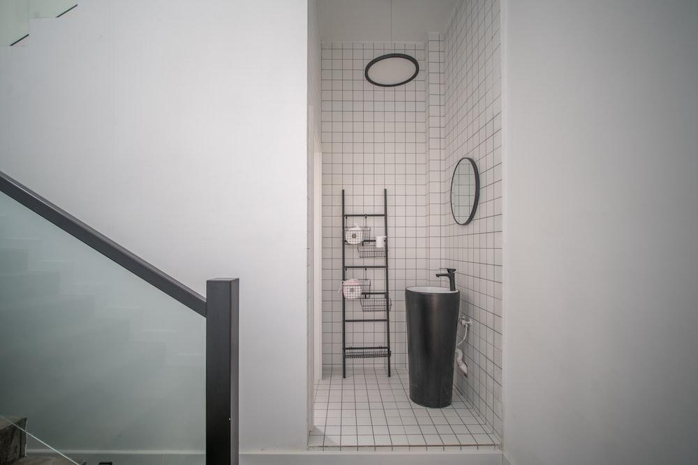 stainless steel trash bin beside white wall