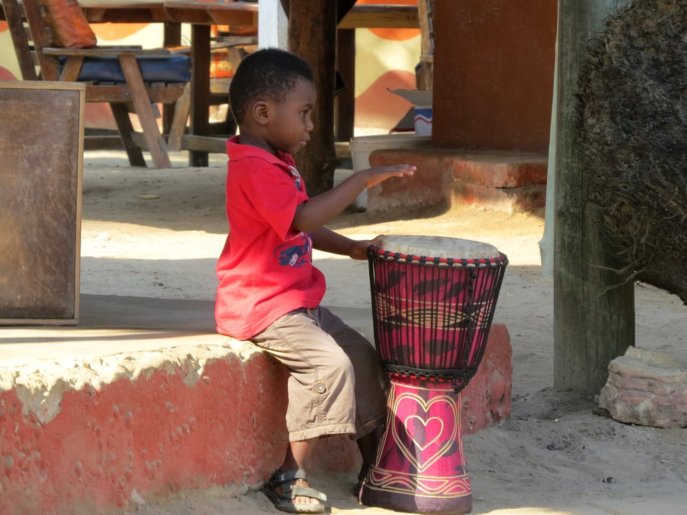 boy in red t-shirt playing drum