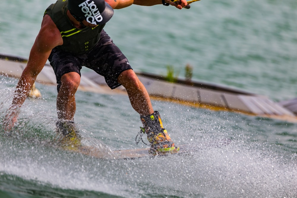 man in black and green tank top and shorts playing skateboard on water during daytime