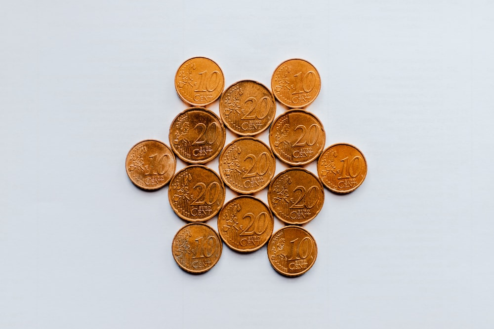 gold round coins on white surface