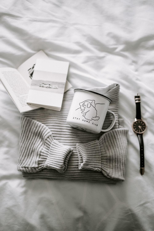 gold round analog watch on white textile