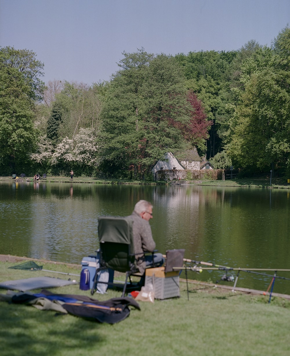 man in gray jacket sitting on green chair near lake during daytime