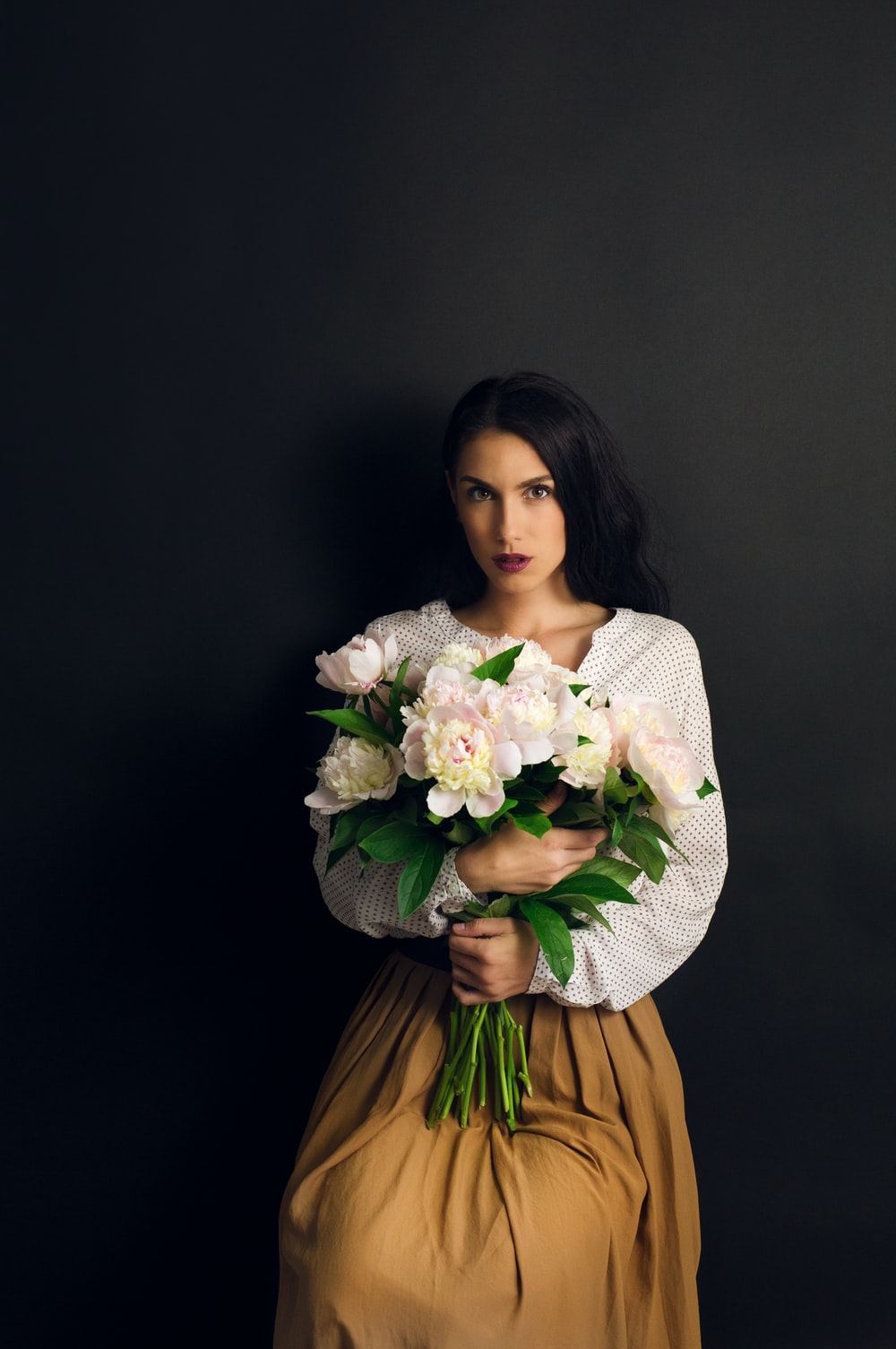 woman in white knit sweater holding bouquet of flowers
