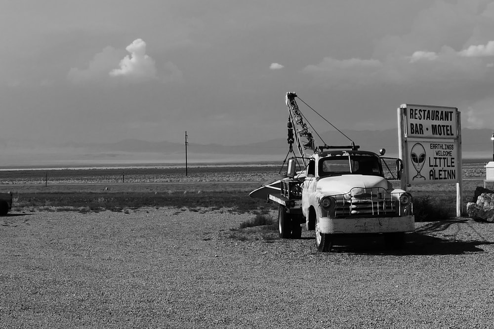 grayscale photo of a truck on a field