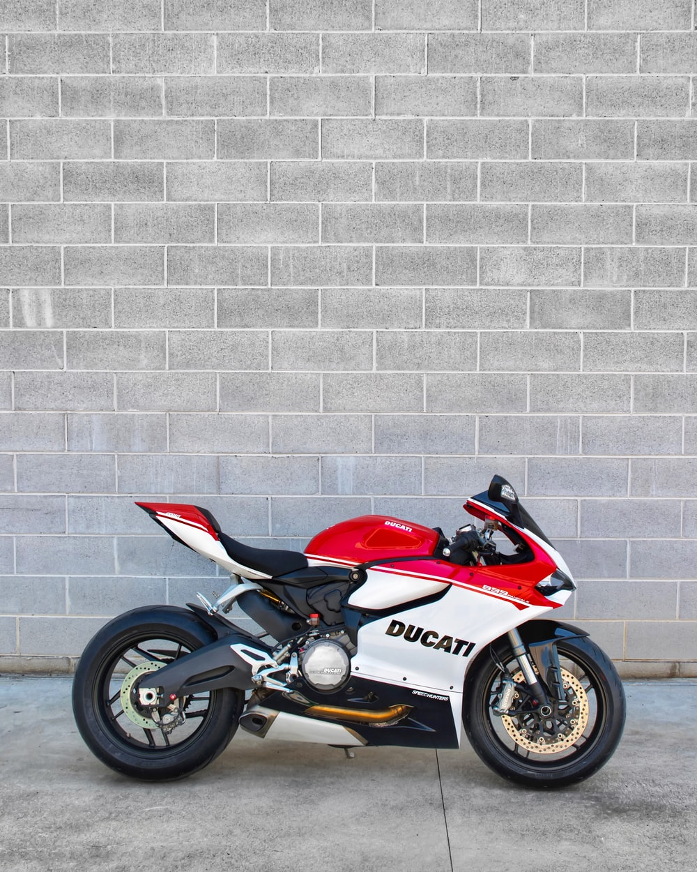 red and black sports bike parked beside white brick wall