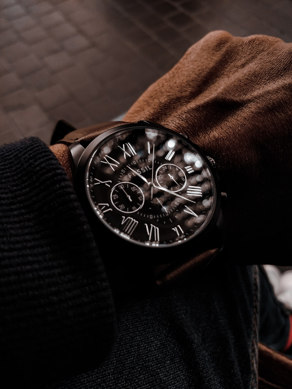 person wearing black leather strap silver round chronograph watch