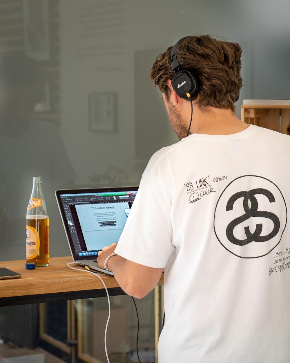 man in white crew neck t-shirt wearing black headphones
