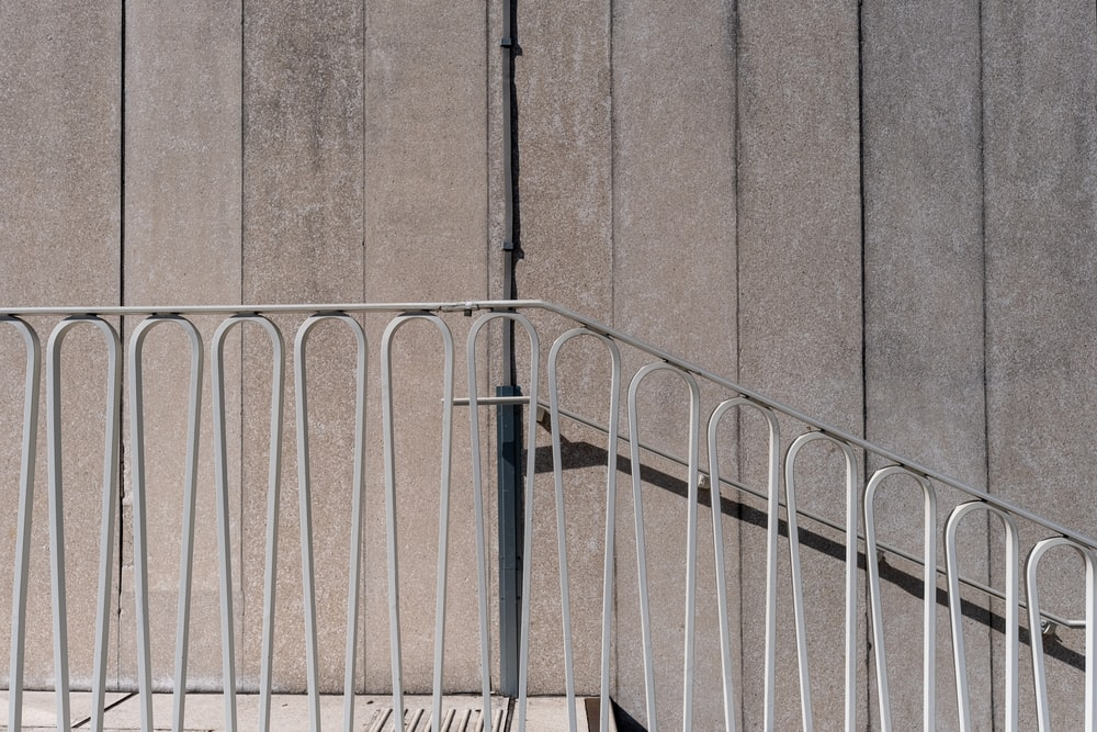 blue metal railings near brown concrete wall