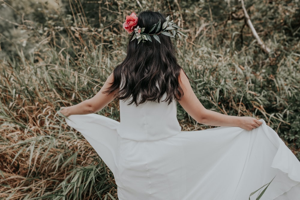 woman in white dress holding red rose