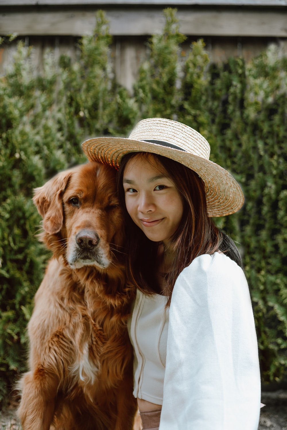 woman in white shirt and brown hat holding brown long coated dog