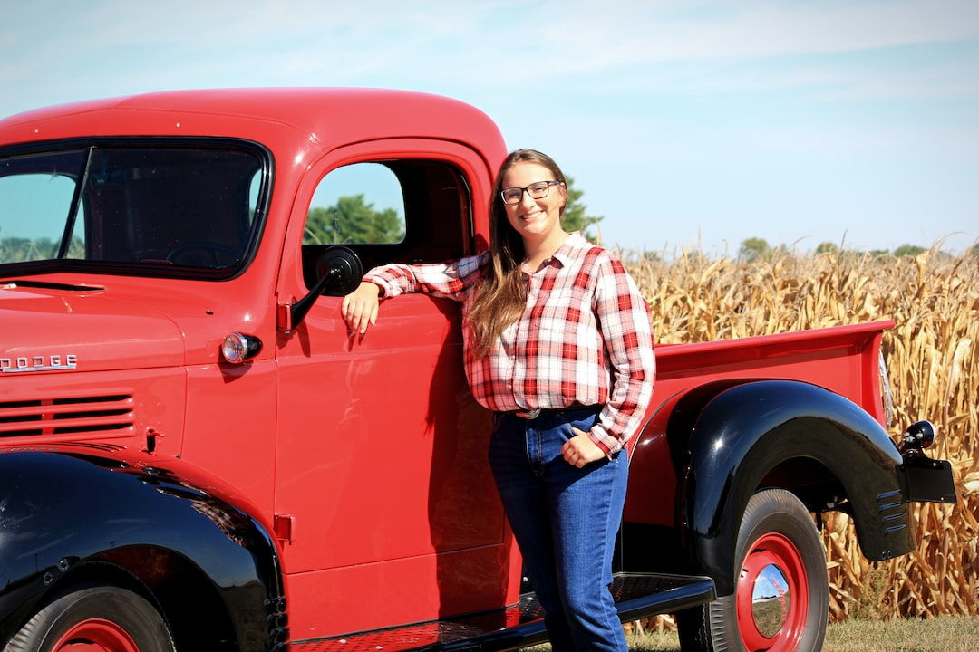 A girl in red flannel and blue jeans leans against a vintage red dodge truck in front of a cornfield.
