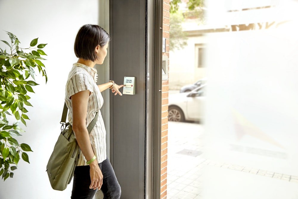 woman in gray t-shirt and blue denim jeans sitting on white wooden framed glass door