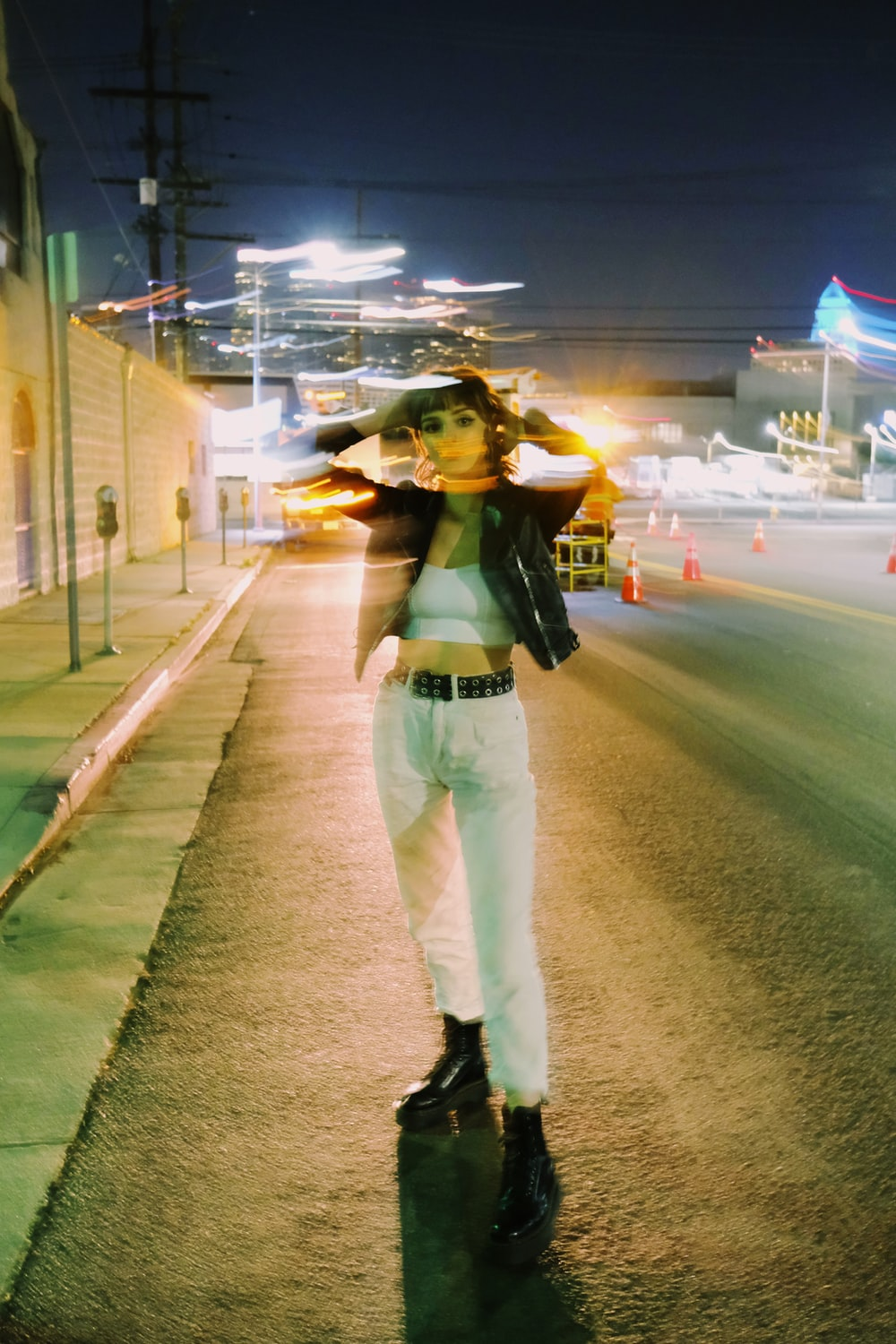 woman in green shirt and white pants standing on road during night time