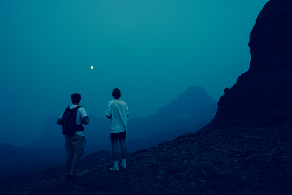 2 men standing on mountain during night time