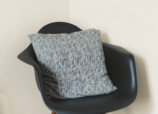 gray throw pillow on black leather chair