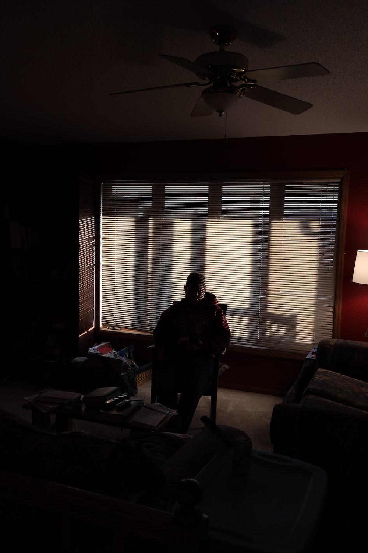 woman in black jacket standing near window