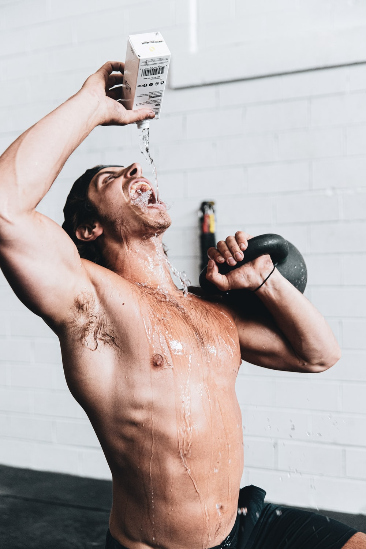 topless man holding black kettle bell