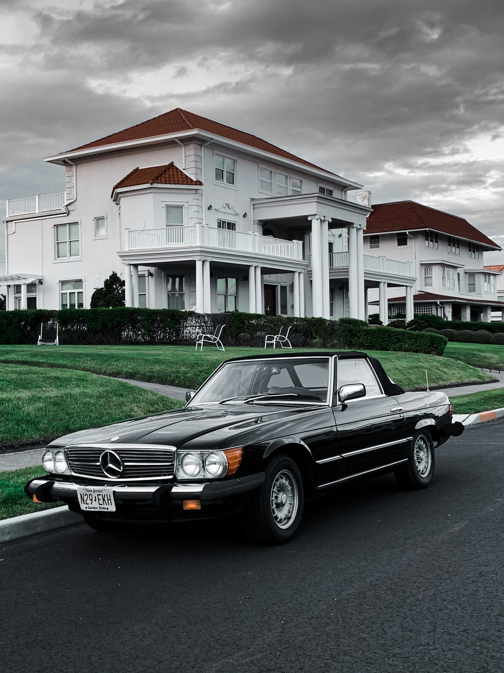 black mercedes benz car parked in front of white and brown house