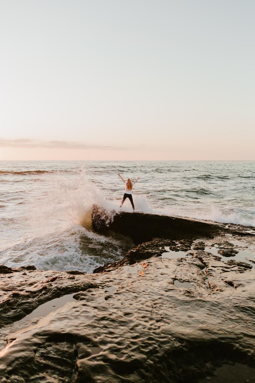 man in orange shirt standing on rock near sea during daytime